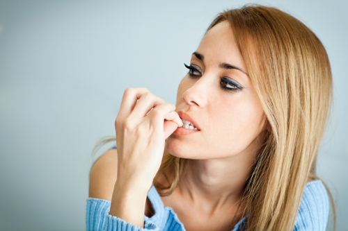 Worried-woman-biting-her-nails Four Habits To Avoid To Enhance Tooth Health