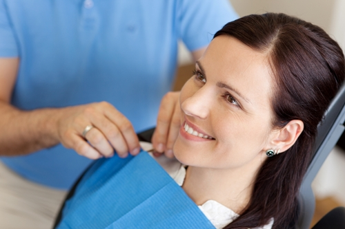 Dentist-Adjusting-Apron-On-Female-Patient-Before-Treatment Great Teeth Boost Personal Confidence
